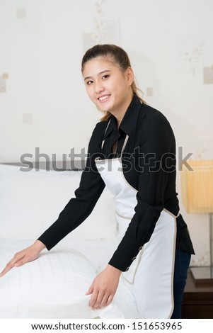 Vertical portrait of a young chambermaid bedding in the apartment - stock photo