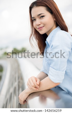 Vertical portrait of a young girl smiling and looking at camera