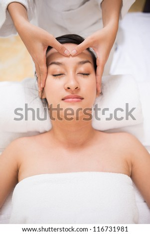 Vertical portrait of a young lady undergoing massage of vital spots - stock photo