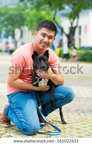 Vertical portrait of a young man hugging his pet in the park and looking at camera  - stock photo