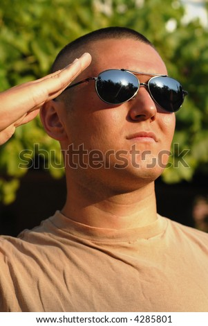 Vertical portrait of a young recruit in boot camp giving a salute - stock photo