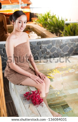 Vertical portrait of a young woman posing in spa salon - stock photo