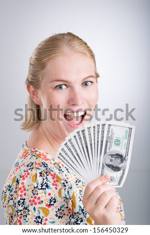Vertical portrait of an emotional young woman with much money in hands