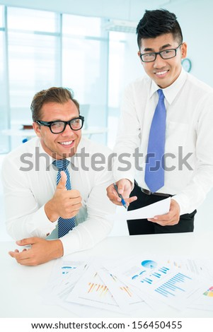 Vertical portrait of business partners smiling and looking at camera while one of them thumbing up  - stock photo