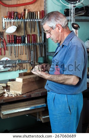 vertical portrait of carpenter examining handmade pieces of wood workshop / work cabinetmaker looking handcrafted wooden pieces finished in garage at home - stock photo