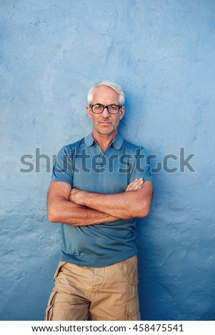 Vertical portrait of confident mature man standing against a blue background. Handsome caucasian man in glasses standing with his arms crossed against a wall. - stock photo