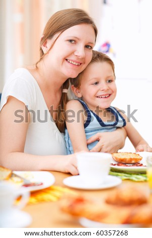 Vertical portrait of happy mother and son having breakfast together