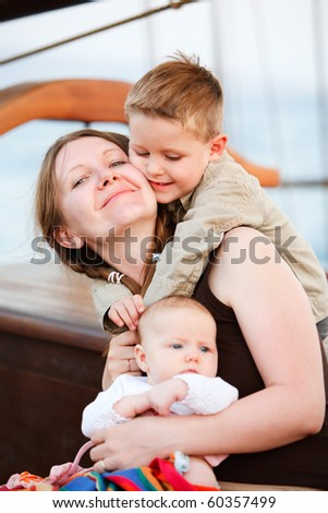 Vertical portrait of loving mother and two adorable kids - stock photo