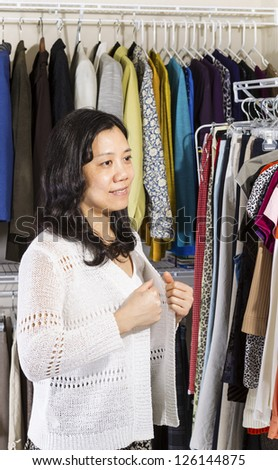 Vertical portrait of mature Asian woman in walk-in closet putting on her white sweater