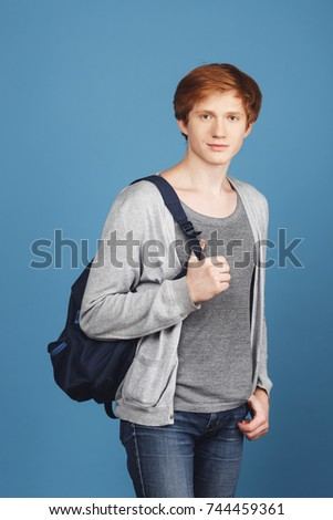 Vertical portrait of serious young red-headed male student in casual gray outfit with black backpack, holding hand in pocket, looking in camera with relaxed and confident expression