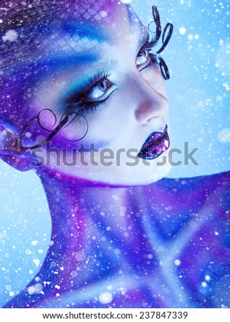 Vertical portrait of young adult girl with creative body art looking away with snow on background in studio - stock photo