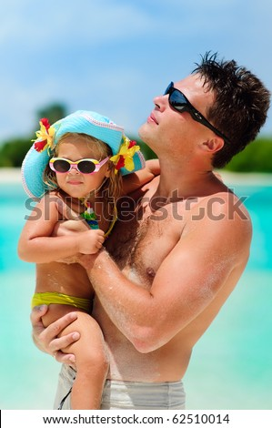 vertical portrait of young athletic father and his cute small daughter in tropical beach background - stock photo