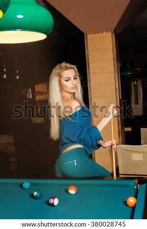 Vertical portrait of young fashionable girl posing on pool table with the cue. Billiard sport concept. Pool billiard game. American pool billiard. - stock photo