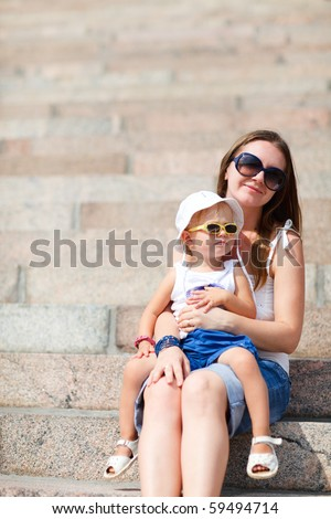 Vertical portrait of young mother and her toddler daughter outdoors - stock photo
