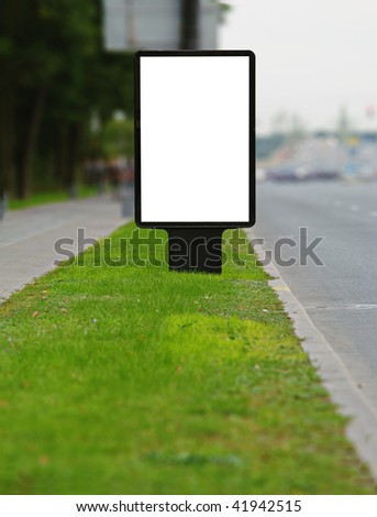 Vertical publicity board on a sward along street - stock photo