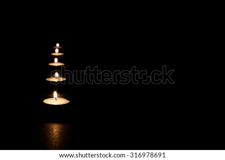 Vertical row of candles burning in the darkness. Selective focus. Copyspace. - stock photo
