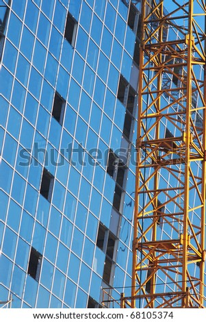 Vertical row of coated blue windows of building under construction with part of yellow tower crane - stock photo