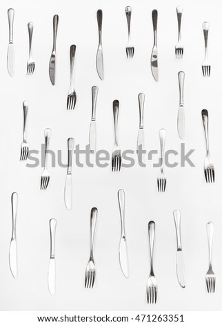vertical set of table knives and forks on white background