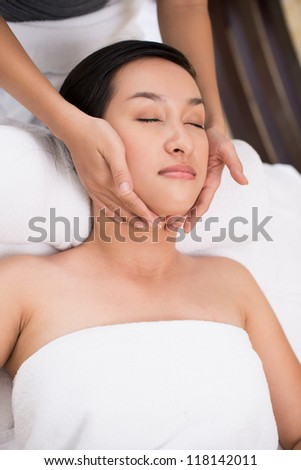 Vertical shot of a beautiful girl enjoying relaxing massage - stock photo