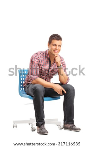 Vertical shot of a casual young guy sitting on a chair and looking at the camera isolated on white background