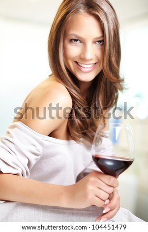 Vertical shot of a cheerful celebrating girl with a glass of wine - stock photo