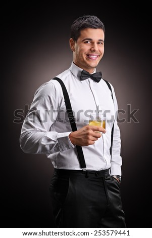 Vertical shot of a cheerful man drinking bourbon on black background - stock photo