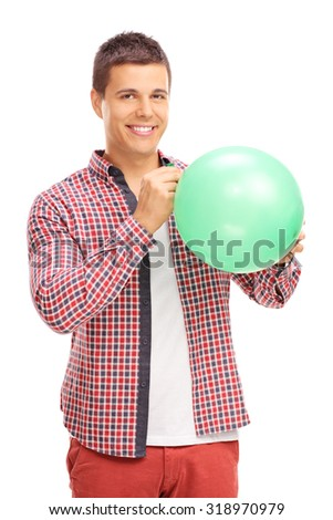 Vertical shot of a cheerful young man blowing up a green balloon and looking at the camera isolated on white background - stock photo