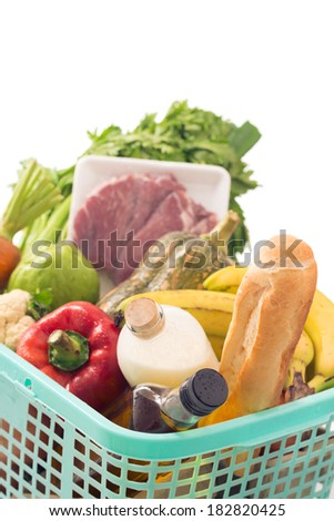 Vertical shot of a customer basket full of basic food products over white  - stock photo