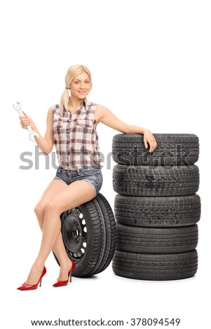 Vertical shot of a female mechanic holding a wrench and sitting on a tire isolated on white background - stock photo