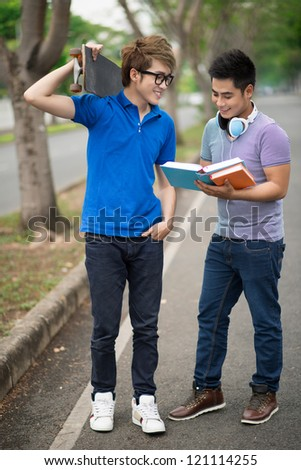 Vertical shot of a guy reading to his skater friend - stock photo