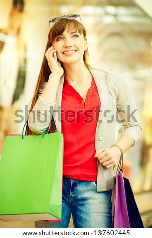 Vertical shot of a happy girl with purchases speaking by the phone - stock photo