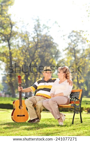 Vertical shot of a husband and wife enjoying a sunny day in park  - stock photo