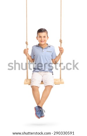 Vertical shot of a joyful little boy sitting on a swing and looking at the camera isolated on white background - stock photo