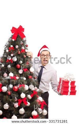 Vertical shot of a joyful man holding three Christmas presents and hiding behind a Christmas tree isolated on white background - stock photo