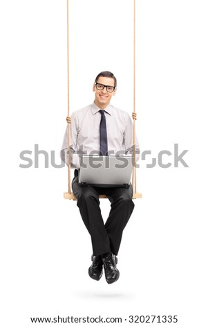 Vertical shot of a joyful young businessman working on a laptop seated on a wooden swing isolated on white background - stock photo