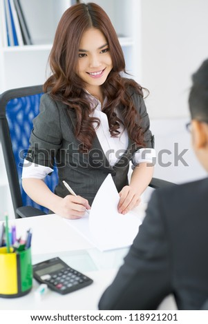Vertical shot of a lovely female employer interviewing a candidate for a vacant position - stock photo