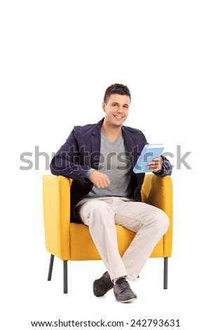 Vertical shot of a man holding a book seated in an armchair isolated on white background - stock photo