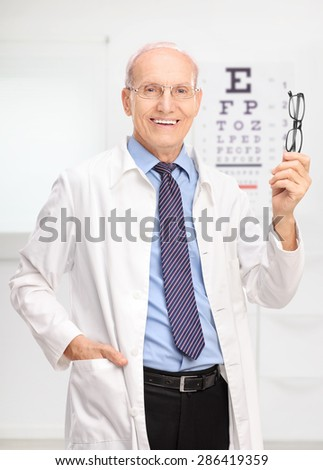 Vertical shot of a mature optician holding a pair of glasses and posing in his office in front of an eye chart  - stock photo