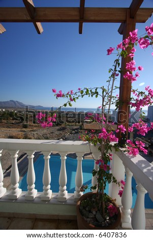 Vertical shot of a mediterranean balcony with pink flowers growing on it, the swimming pool beneath it and the sea in the distance. Taken in the Greek island of Rhodes - stock photo