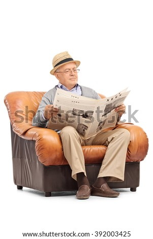 Vertical shot of a relaxed senior gentleman reading a newspaper seated on an armchair isolated on white background - stock photo