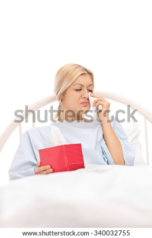 Vertical shot of a sad female patient lying in a hospital bed and crying isolated on white background - stock photo