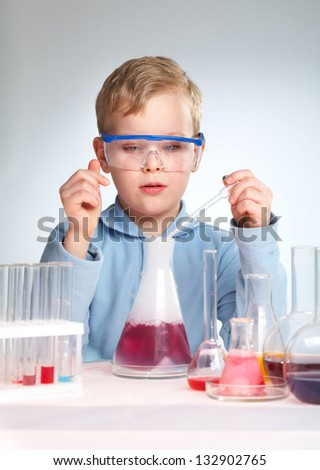 Vertical shot of a school scientist being curious about chemical reaction - stock photo
