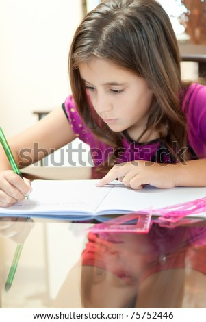 Vertical shot of a small girl wearing shorts and a t-shirt working on her school project at home - stock photo