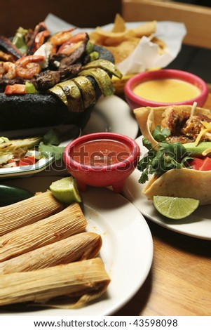 Vertical shot of a variety of Mexican dishes. Shallow dof with central portion of image in focus. - stock photo