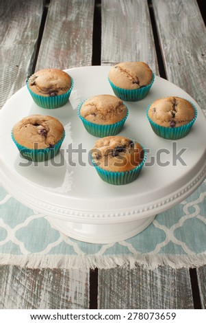 Vertical shot of a white cake stand with fresh homemade blueberry whole wheat muffins on an old barn wood table - stock photo