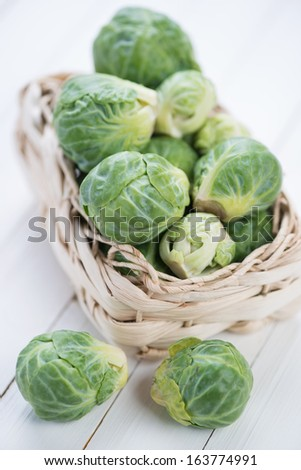 Vertical shot of a wicker basket with brussels sprouts - stock photo