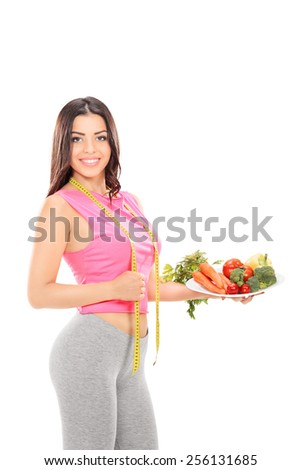Vertical shot of a woman holding a plate full of vegetables isolated on white background - stock photo