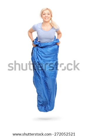 Vertical shot of a young blond woman jumping in a blue sack isolated on white background - stock photo