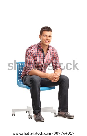 Vertical shot of a young cheerful man sitting on a blue chair isolated on white background - stock photo