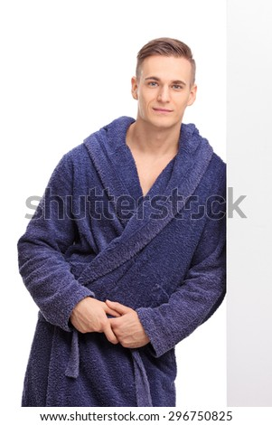 Vertical shot of a young man in a blue bathrobe leaning against a wall and posing isolated on white background